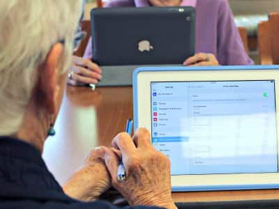 Elderly man using iPad internet screen with aged hands