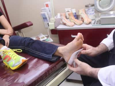 a doctor fitting a patient for orthotics