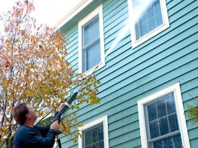 A man power washes a house.