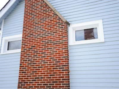 a brick chimney on the side of a blue house with two windows