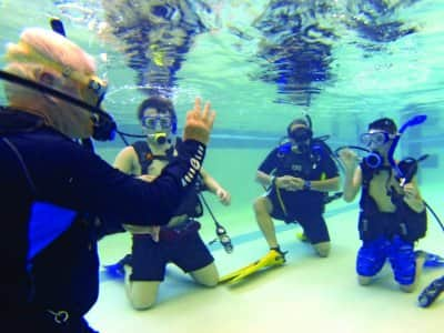 man teaches divers in swimming pool