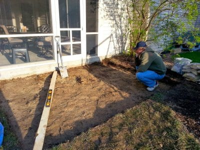 man digging paver patio foundation