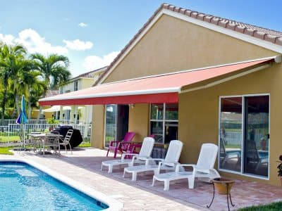 retractable awning covers poolside patio area with lounging chairs in the backyard of a house.