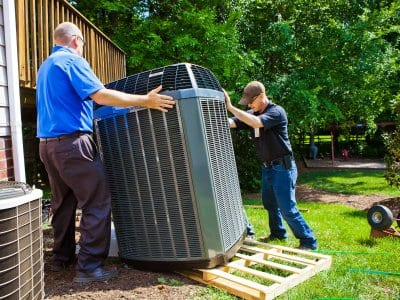 two men installing an HVAC unit