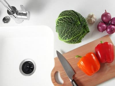garbage disposal in sink with vegetables and knife on cutting board