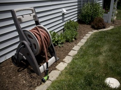 A garden hose sits outside a house/