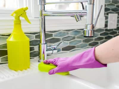 Hand scrubbing white sink with yellow sponge
