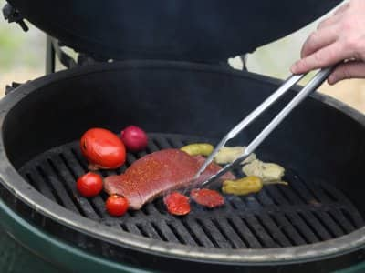 man tendin a steak and vegetables on a grill.