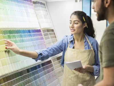 a paint store clerk helps a customer pick a paint color