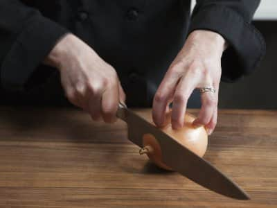 chopping an onion on cutting board