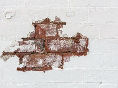 chipped white Limewash paint exposing brick