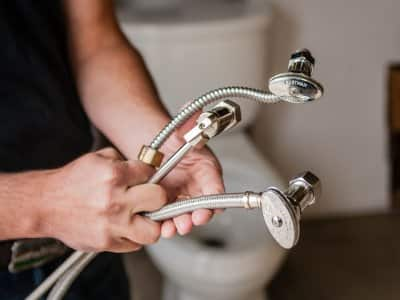 plumber holding supply lines and valves