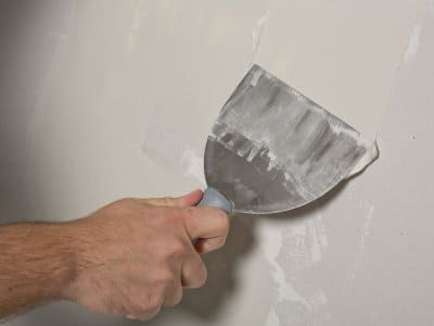 hand using putty knife