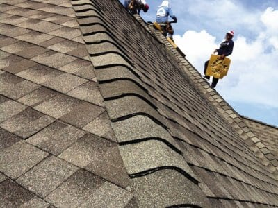 workers install asphalt shingles on roof