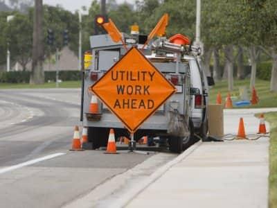 "a ""utility work ahead"" sign with work trucks lined up around a sewer line repair"
