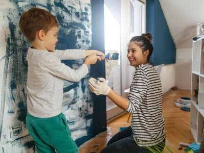 a woman and child painting a wall