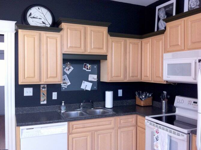 kitchen with light wood cabinets dark countertop and backsplash