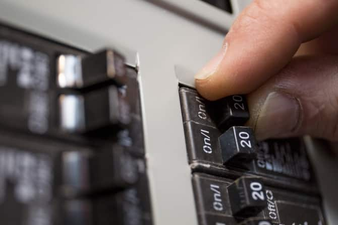 hand switching off an electrical circuit breaker