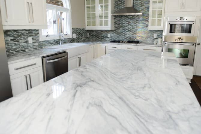 Kitchen With White Marble Countertops And Tile Backsplash