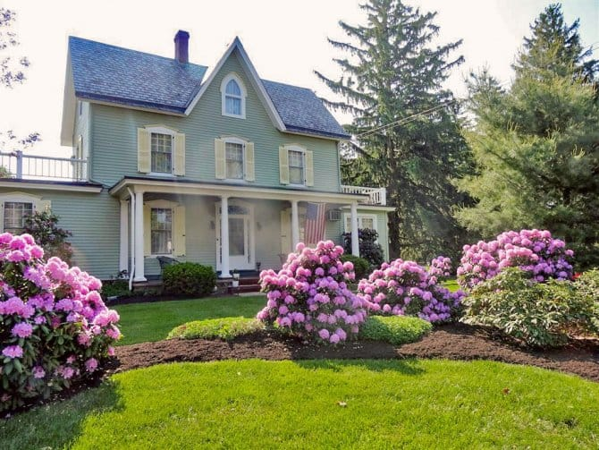 Victorian home landscaped with pink peony bushes | Angie's ...