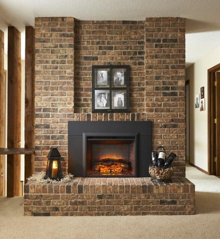 electric fireplace with brick surround and family photos mounted above