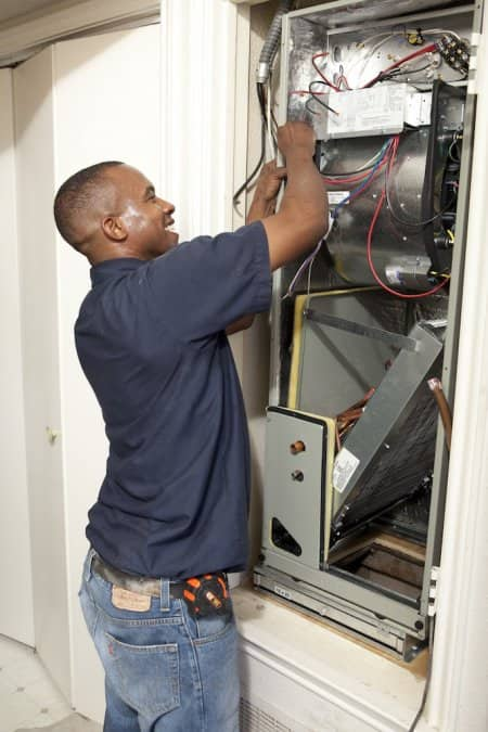 HVAC professional making electrical connections on Trane air handler