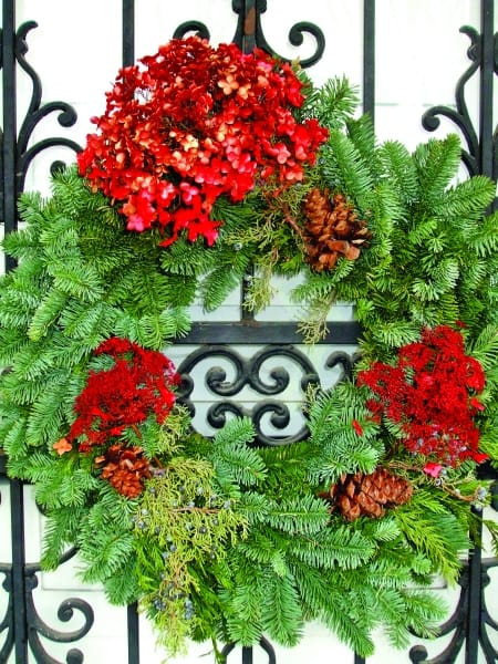 greenery wreath with holiday decorations on door