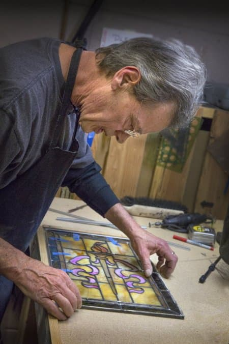 The Front Gate glass expert Gary Zelinger working on stained glass for a restored door