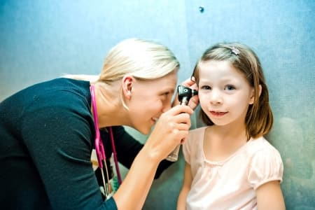 pediatrician examines a child's ear