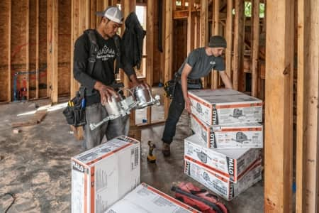 electricians installing wiring in a new home