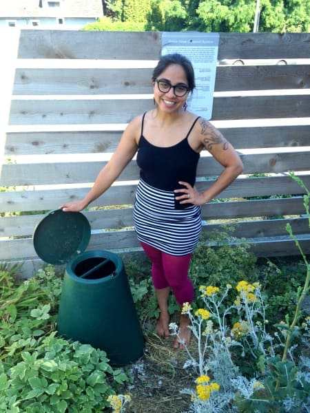 woman standing in garden by compost system