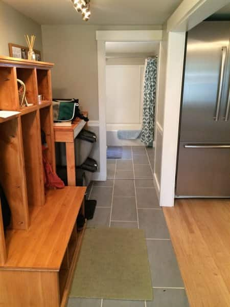 mudroom with custom cubbies adjacent to a kitchen and bathroom