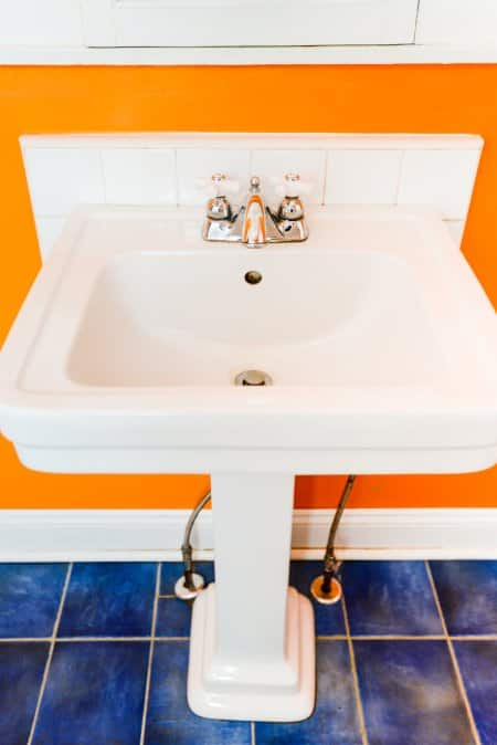 White Bathroom Pedestal Sink Shot From Front To Show Supply Lines  Connecting To Floor On Either