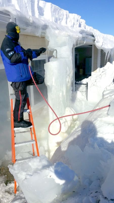 ice dam removal contractor on ladder removes gutter icicles