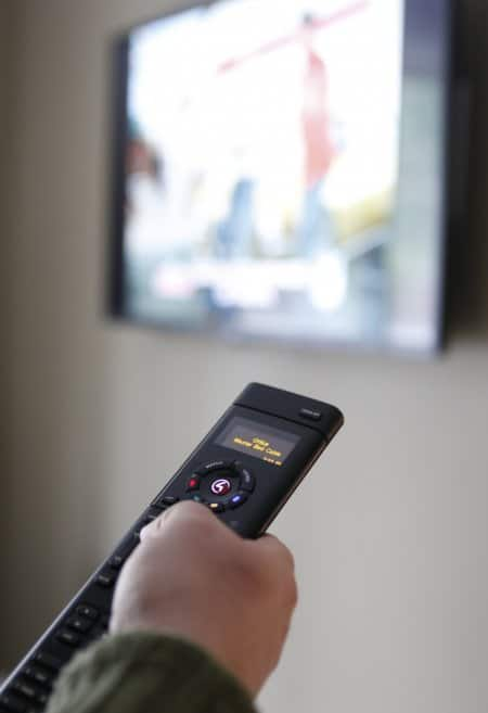 Universal remote held in user's hand, pointing at TV in soft focus