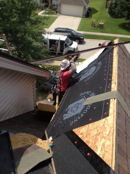 roofing contractor installing new roof sheathing and felt paper