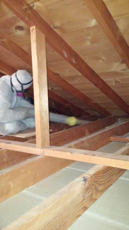 worker installing insulation in attic