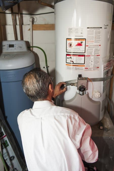home inspector looking at water heater