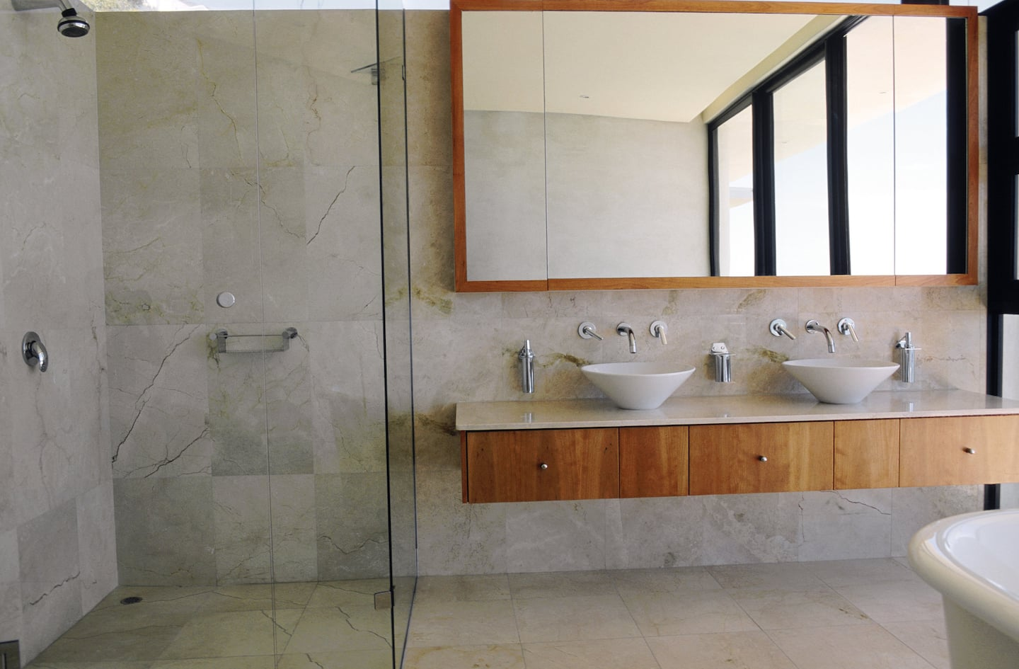 a modern looking bathroom scene with two bowl sinks on a wood faced shelf counter - Bathroom Cabinets Ideas