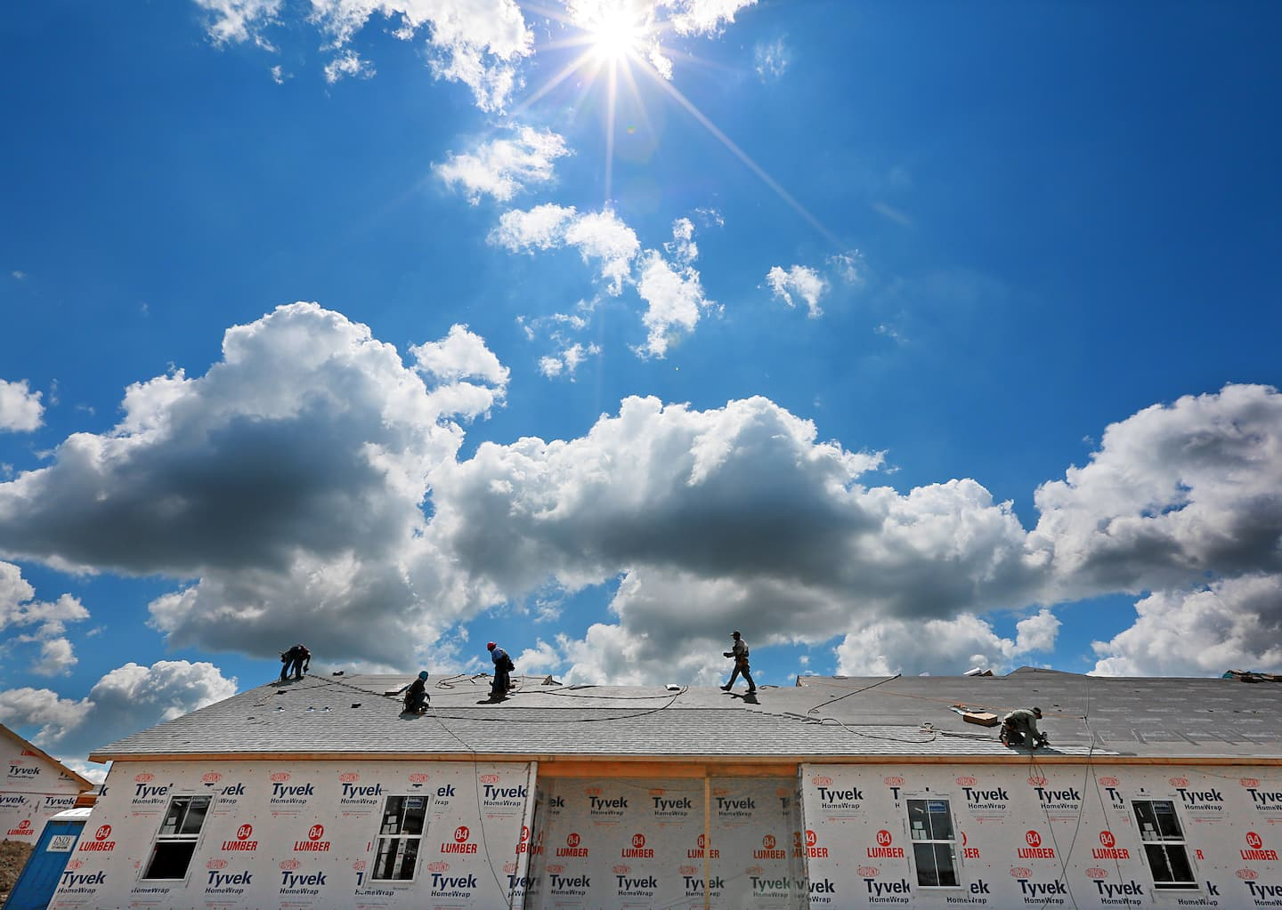 Roofers on a roof with the blue sky and sun shining