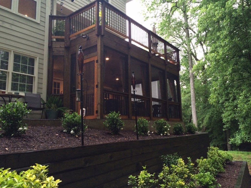 Open deck over rustic screened in porch, flanked by raised flowerbed.