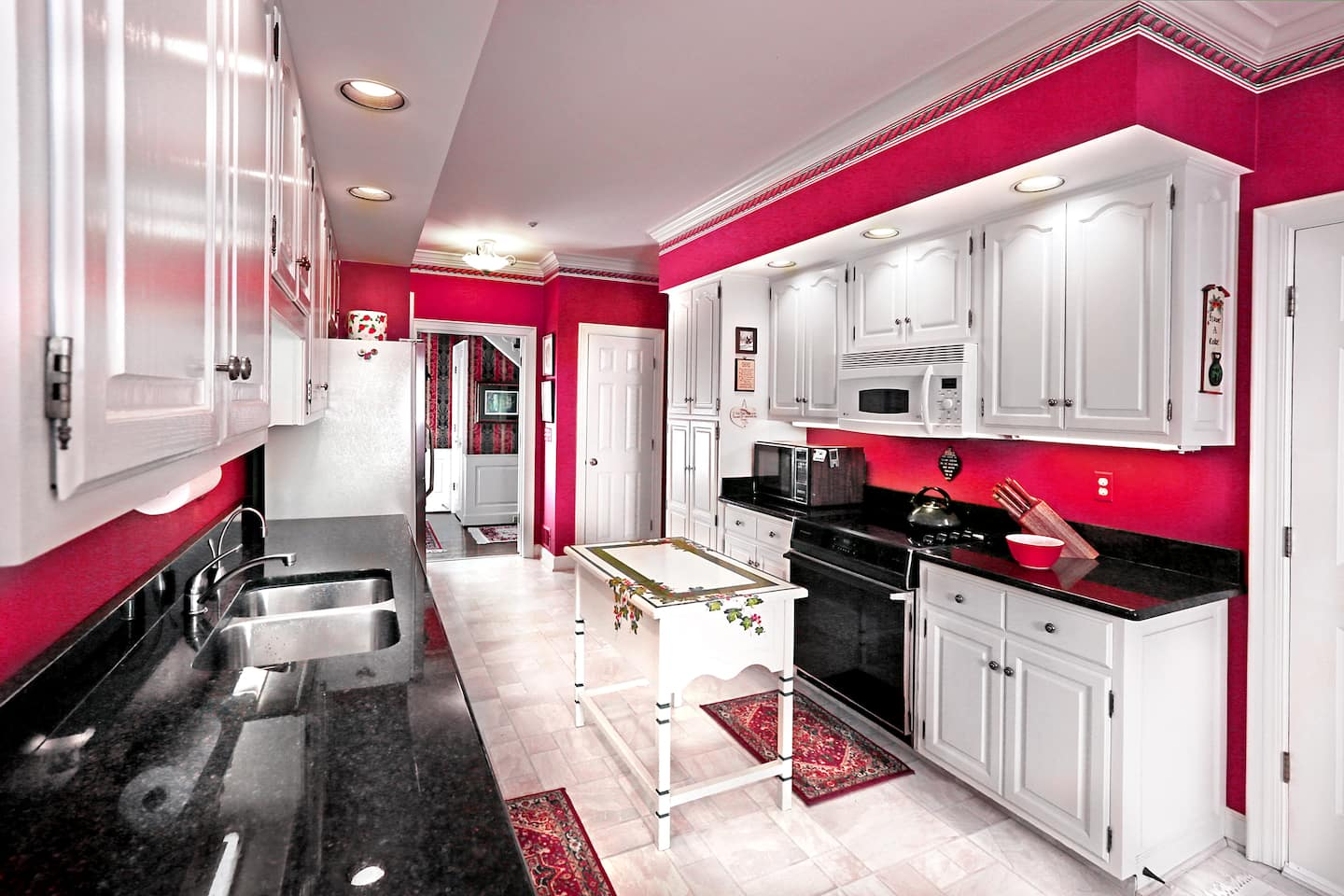kitchen with red walls and white cabinets
