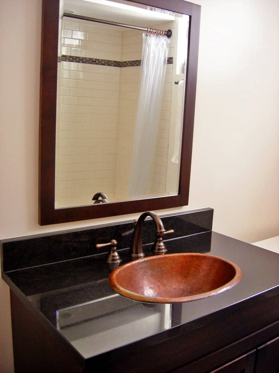 bathroom vanity with 17inch oval copper sink and black counter