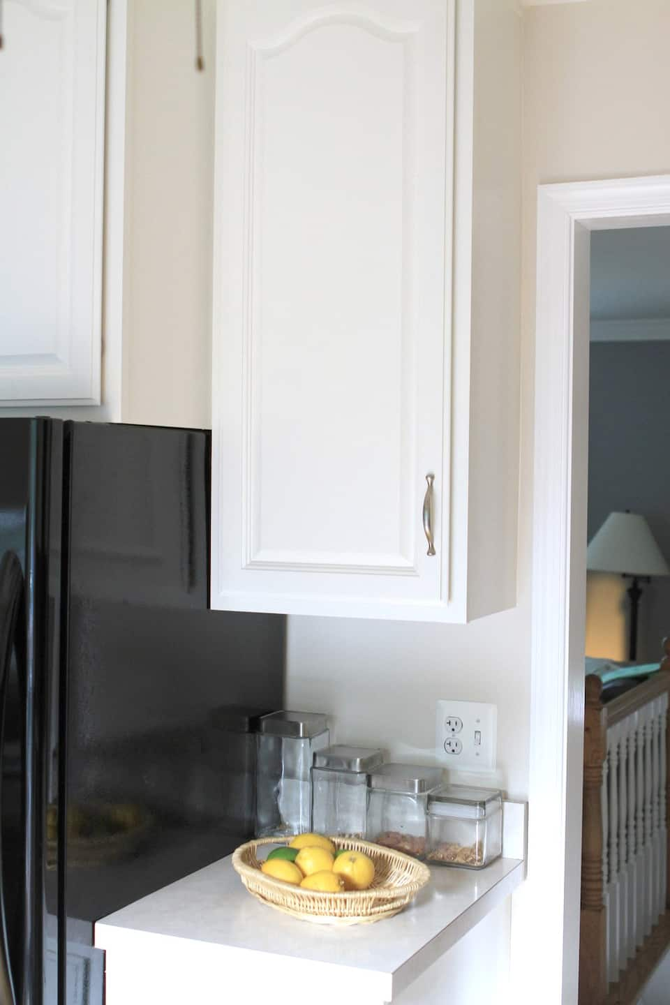 tall white kitchen cabinet with fruit on counter below