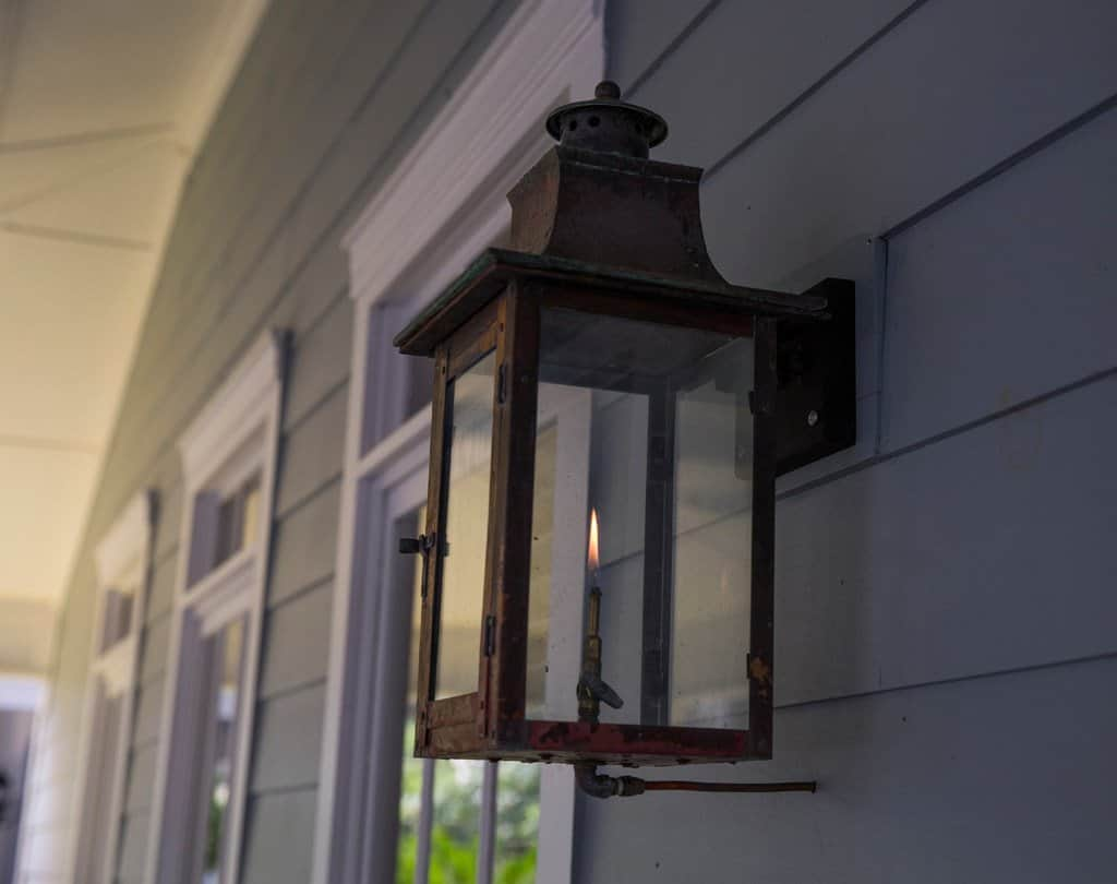 close up of a gas light porch light on house