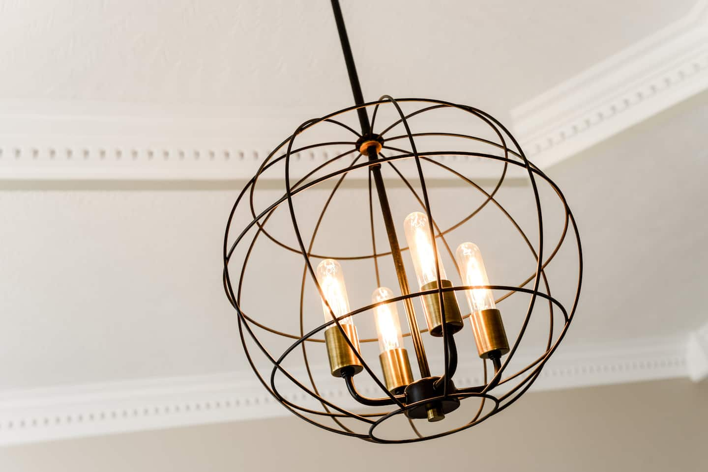 A wire frame light with four bulbs hangs from the ceiling