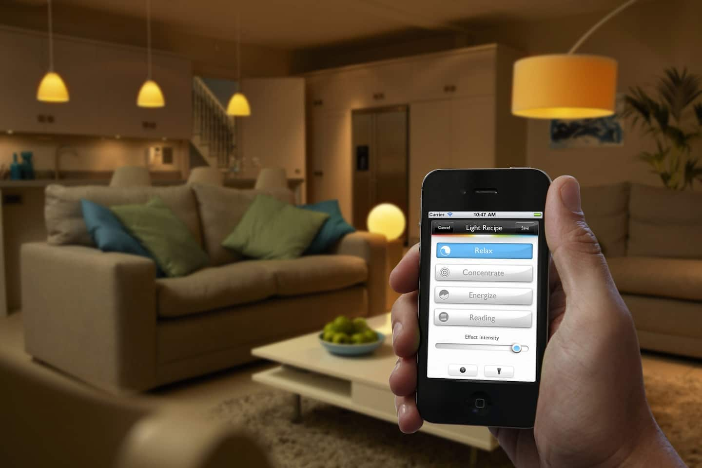 A hand holding a smartphone that homeowners can control their interior lights from using the app on the screen.