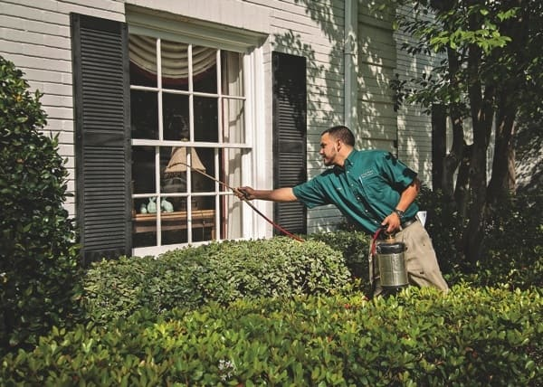 A Long Point Pest Control service technician sprays the perimeter of a house from outdoors for clients who don't want chemical sprays inside their home. (Photo courtesy of Long Point Pest Control)