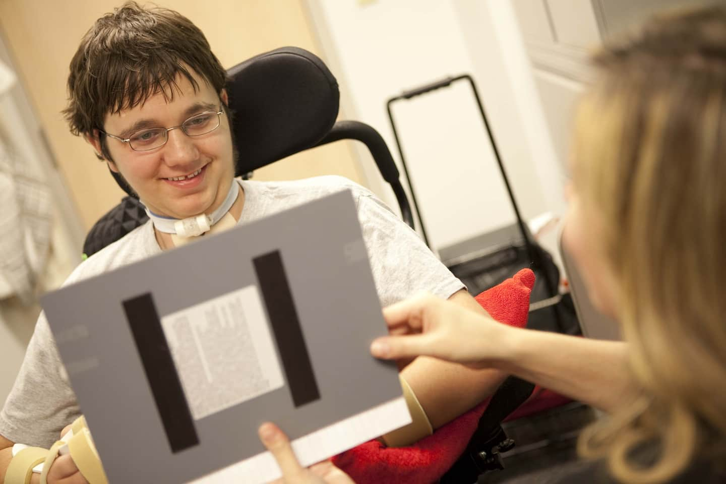 young man in wheelchair working with speech therapist