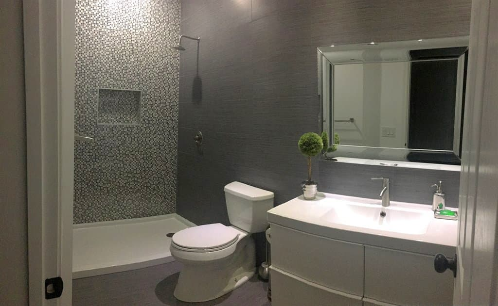 Remodeled bathroom with recessed vanity lights, under-cabinet lighting, and shower light